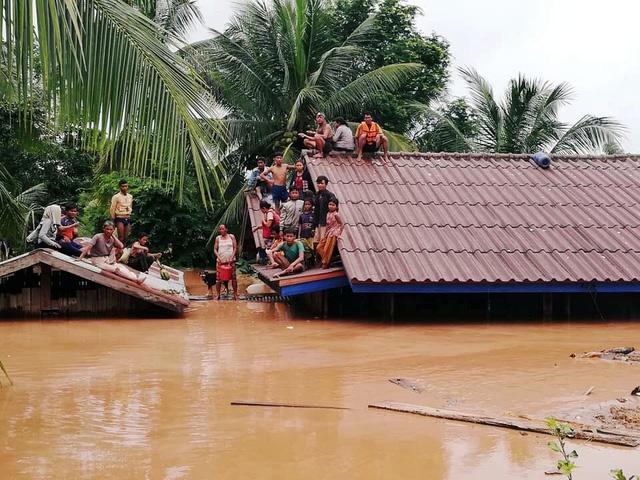 Người dân Lào tập trung trên mái nhà chờ cứu hộ sau sự cố vỡ đập thủy điện (Ảnh: Reuters)