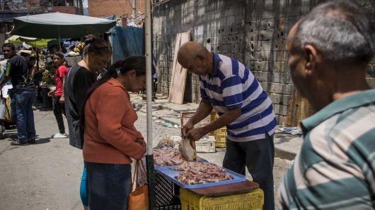 Một người bán thịt ven đường tại thủ đô Caracas, Venezuela (Ảnh: AFP)