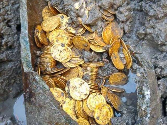 Các đồng tiền vàng sáng bóng đựng trong một chiếc lọ có 2 tay cầm từ thời La Mã chôn dưới lòng đất. Ảnh: Bộ Văn hóa Ý
