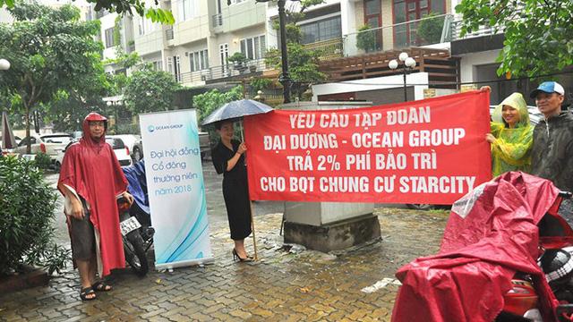 Cư dân chung cư Star City ở 81 Lê Văn Lương đội mưa căng băng rôn đòi quỹ bảo trì. Ảnh: Thanh Niên.