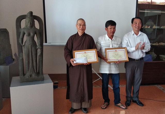 Phó Chủ tịch UBND tỉnh Vĩnh Long (phải) trao tặng Bằng khen và số tiền 75 triệu đồng cho hai cá nhân phát hiện và tự nguyện giao nộp tượng nữ thần.