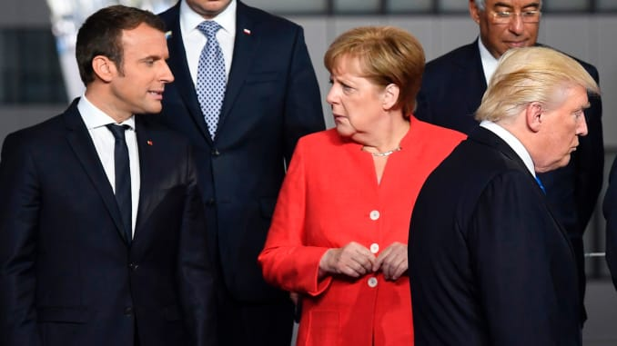 French President Emmanuel Macron (L) and German Chancellor Angela Merkel (2nd L) speaks as US President Donald Trump (C) arrives for a family picture during the NATO (North Atlantic Treaty Organization) summit at the NATO headquarters, in Brussels, on May