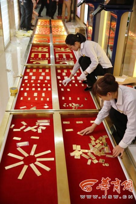 Các nhân viên tiệm vàng tỉ mỉ xếp từng thỏi vàng vào vị trí