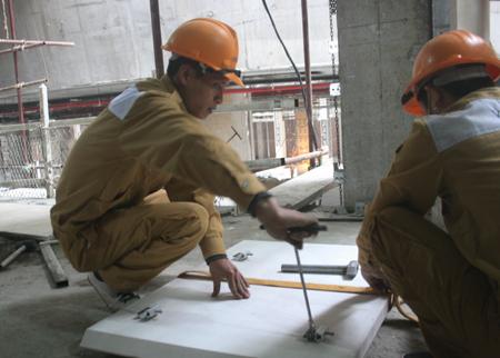 Các công nhân treo đá ốp cột, xà của công trình