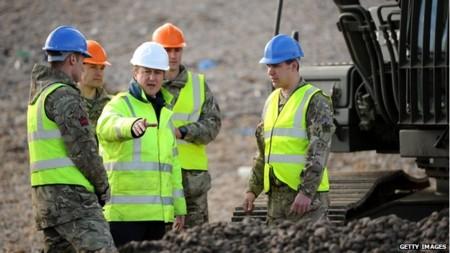 Chính phủ của thủ tướng Cameron (mũ trắng) đang đối diện nhiều chỉ trích về ứng phó với lũ lụt