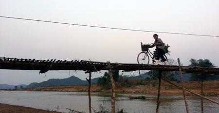 Một người phụ nữ Làng Dũa đi làm về trên chiếc cầu khỉ.