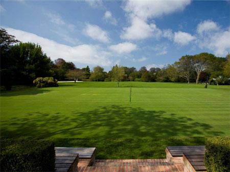 Sân tennis mặt cỏ nằm kề sân sau.