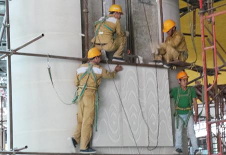 Công nhân thi công hạng mục treo đá ốp tường, cột tại đại sảnh tòa nhà.