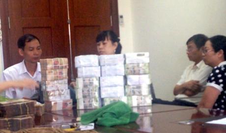 Ông Đinh Ngọc Uyên, Phó GĐ Công ty TNHH MTV Cảng Quảng Ninh (áo trắng khoanh tay) giao nộp tiền cho cơ quan chức năng. (Nguồn ảnh QNO)