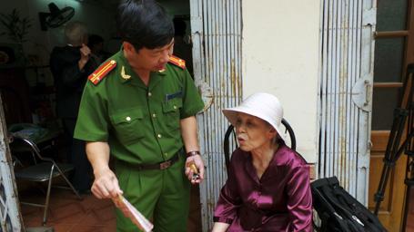 Những người già được cán bộ công an tận tình hướng dẫn các thủ tục để làm chứng minh thư.