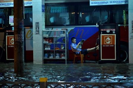 Nhân viên cây xăng ngồi chơi đọc báo vì nước ngập không có khách