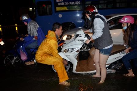 Nhân viên thoát nước giúp người dân đưa xe qua vùng ngập