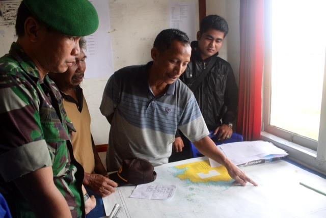 Một quan chức quân đội Indonesia thảo luận với người dân về vụ máy bay mất tích.