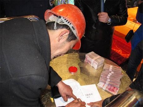 Các công nhân ký nhận trước khi lĩnh tiền.