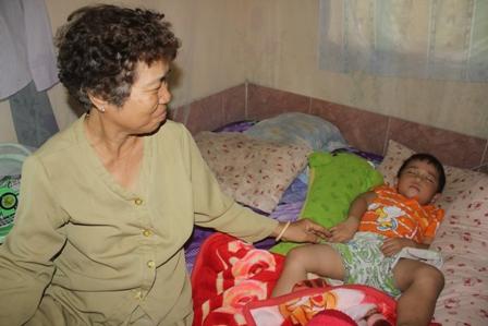 Bà Mậu đang chăm sóc đứa cháu nội mới 3 tuổi luôn khóc đòi cha