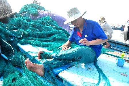 Ngư dân trên tàu cá QNg 94537TS của ông Ngô Tiên (Quảng Ngãi) tranh thủ vá lại lưới
