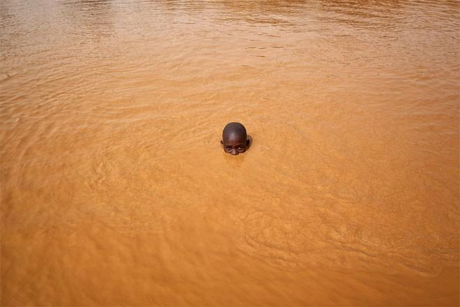 Abdul Haruna, 14 tuổi, là một trong số hàng trăm đứa trẻ làm việc ở mỏ vàng Djuga. Cậu bé đang tắm sau một ngày làm việc dài.