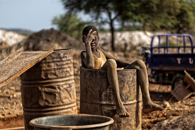 Sau nhiều giờ lao động vất vả ở mỏ vàng, Nuru Haruna, 13 tuổi, ngâm mình trong một thùng nước.