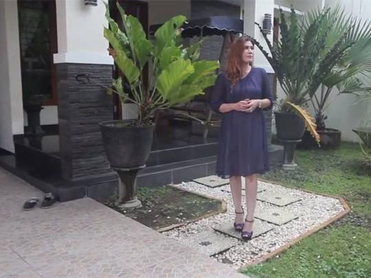 Bà Wina Lia đứng trước ngôi nhà đang rao bán của mình. Ảnh: Independent