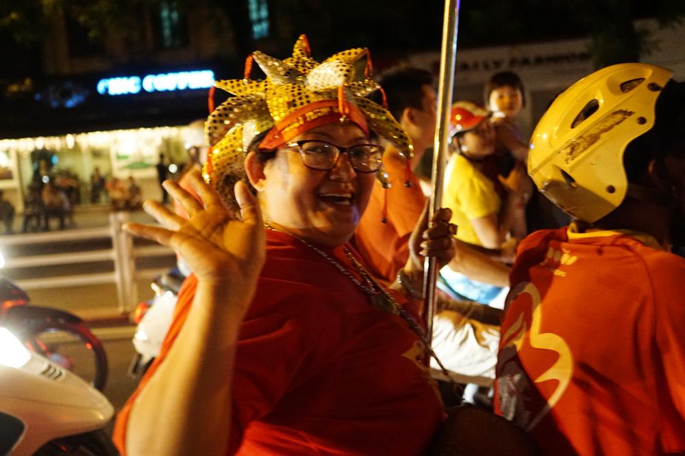 Một người hâm một đi trong đoàn diễu hành với chiếc mũ của chú hề.