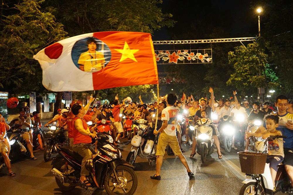 Lá cờ ghép đôi Việt Nam - Nhật Bản cùng HLV Miura bay phất phới trên đường phố.