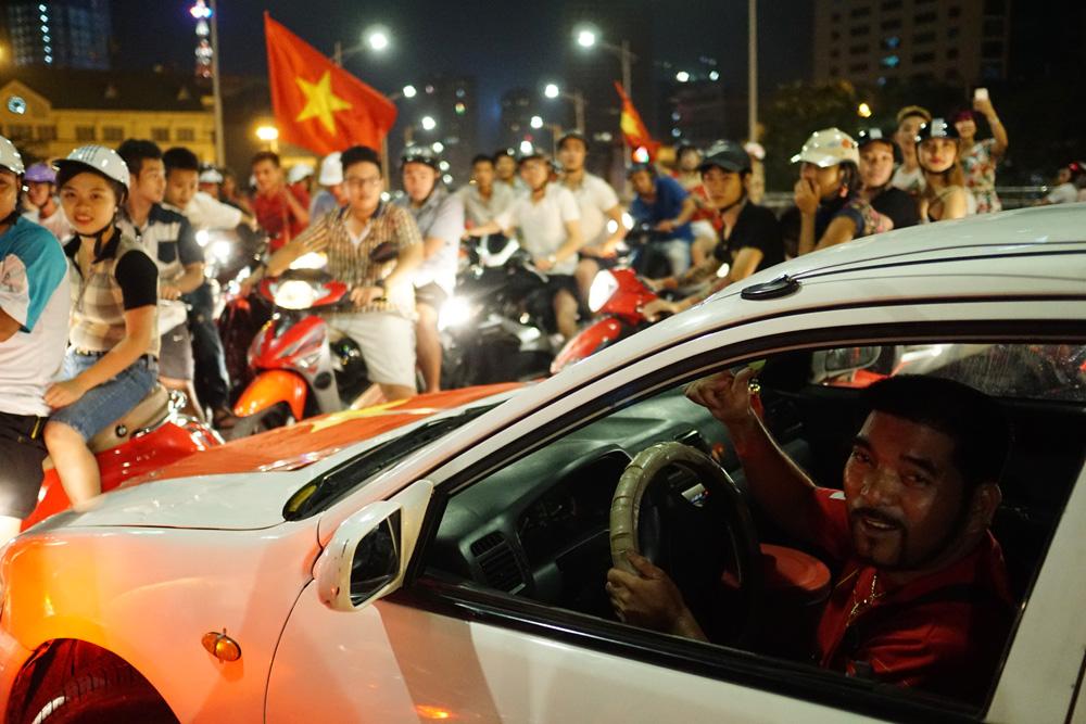 Một chiếc xe ô tô của người hâm mộ dẫn đầu đoàn diễu hành xe máy đầy phấn khích.