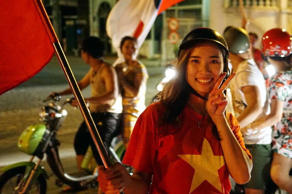 Một nữ cổ động viên xinh đẹp phất cao lá quốc kỳ trên đường phố.