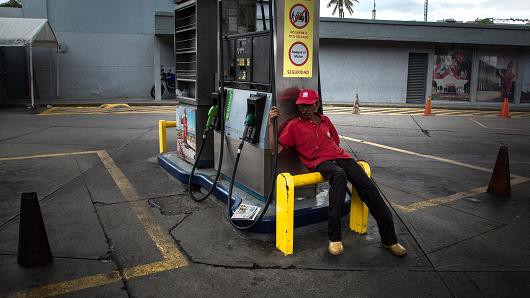 Một nhân viên ngồi thất thần tại trạm xăng Petroleos de Venezuela tại Caracas, Venezuela. (Nguồn: Wil Riera | Bloomberg | Getty Images)