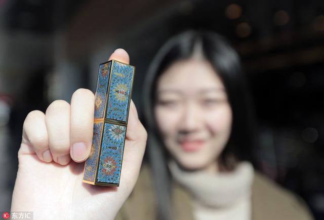 Xiao Tian đang cắt một miếng dán để trang trí thỏi son cho khách hàng. (Nguồn: IC)
