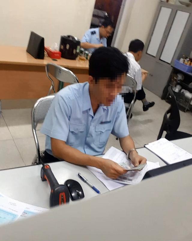 """Một nhân viên hải quan đang kiểm tra số tiền hàng triệu đồng vừa được nhân viên """"chạy lệnh"""" nhanh chóng đưa vào."""